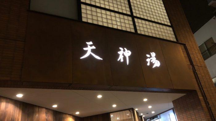入口はこんな感じ。木目調で高級感あふれる外装。書体とライトの感じも相まって高級に見えるのでしょうか。/天神湯