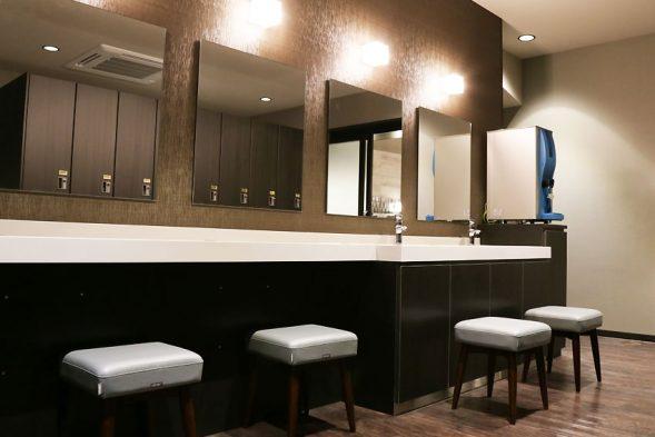 給水器とアメニティのある鏡台。床はタオルで覆われている。水浸し対策。おもてなしのお宿HPより